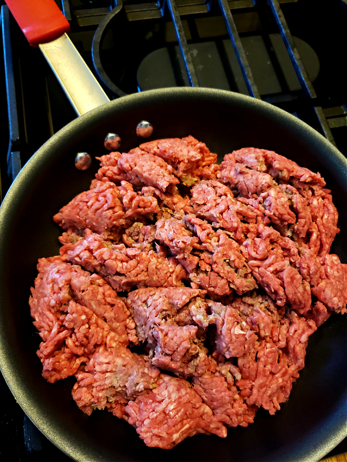 cooking minced beef in a skillet on a gas cook top