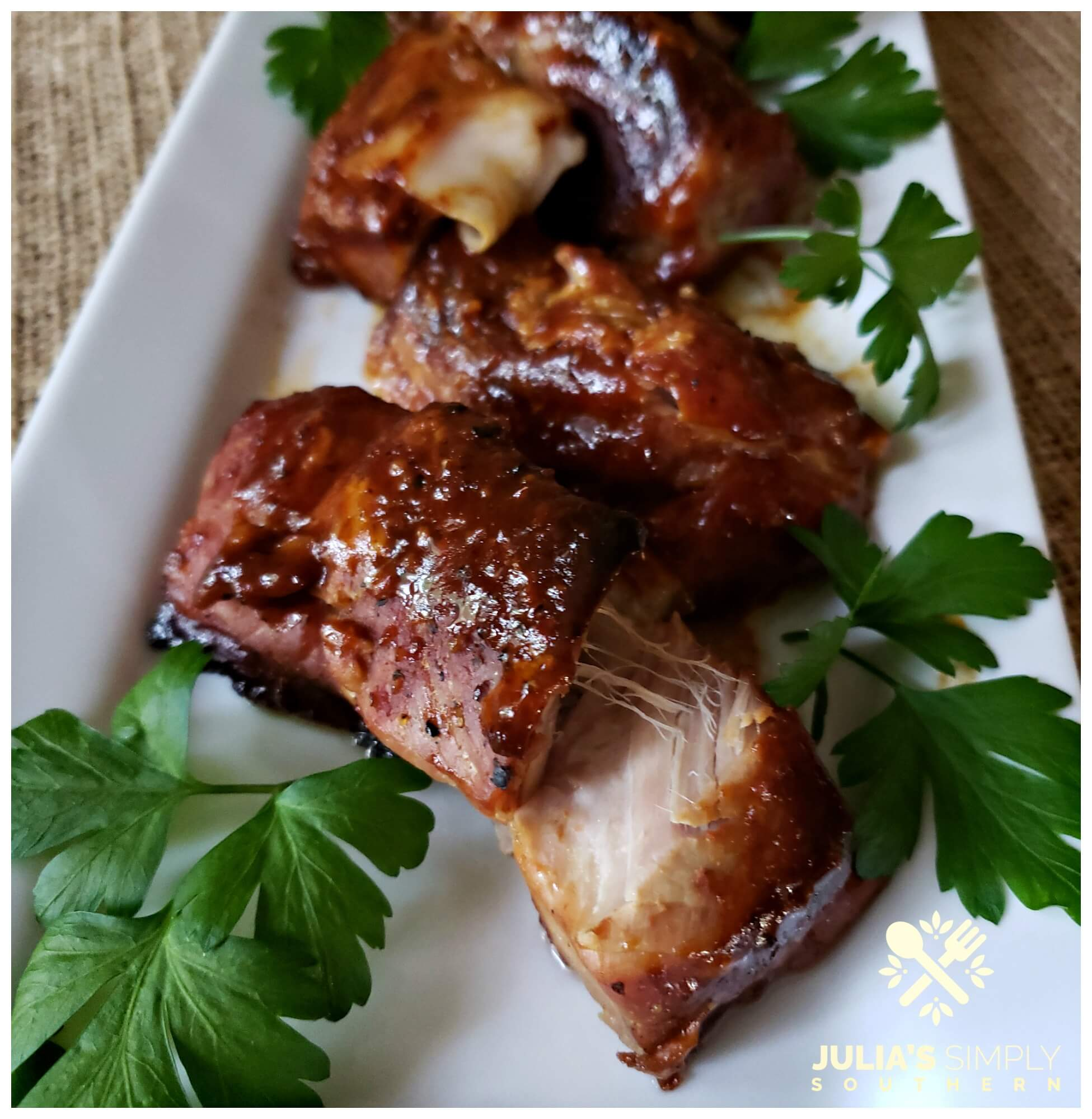 Tender boneless Easy Country-Style Pork Ribs Recipe with BBQ cooked slow in the oven until they are tender and fall apart delicious. Served on a white platter garnished with parsley.