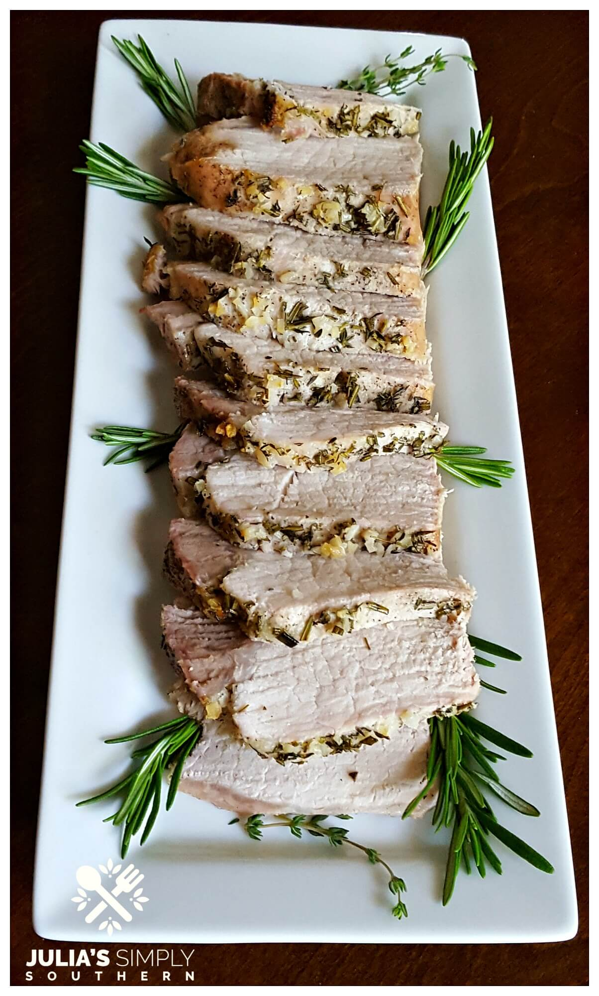 White platter with sliced pork loin roast crusted with herbs and garlic