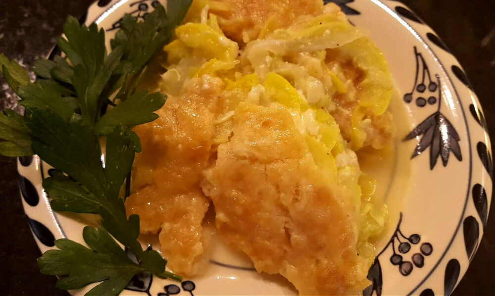 Southern style squash casserole on a plate garnished with vegetable greenery