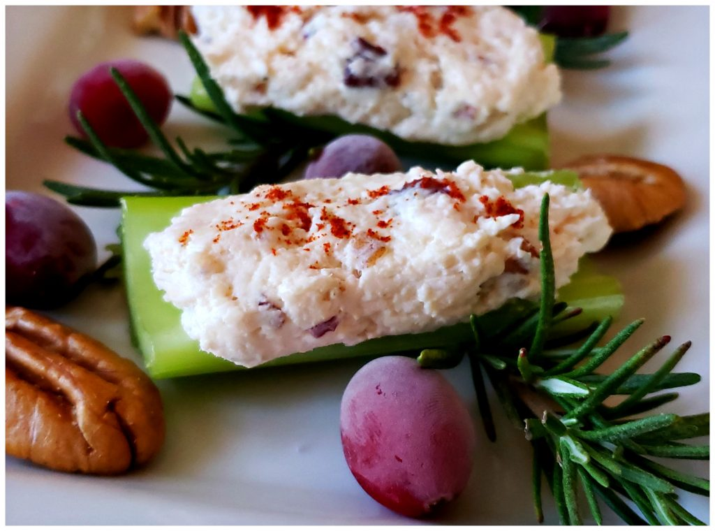 delicious stuffed celery appetizer on a white platter sprinkled with paprika