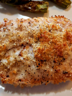 Panko Parmesan Baked Pork Chops on a plate with baked asparagus